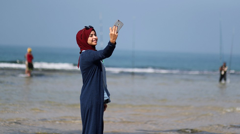 Fatma Abu Musabbeh uses her mobile phone to take a selfie on a beach in the central Gaza Strip (Photo: Reuters)