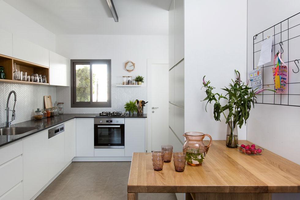 המטבח אחרי השיפוץ, עם ארונות ואריחים חדשים. דלפק ישיבה מעץ אורן הוצמד לארונות הגבוהים  (צילום: שירן כרמל)