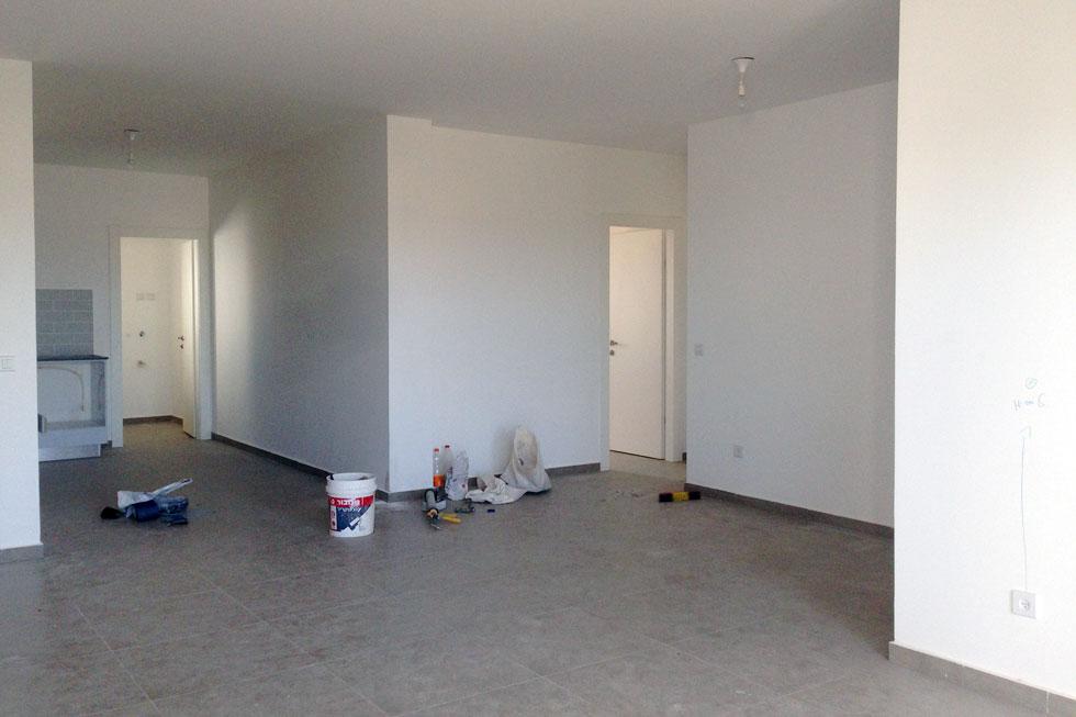 """כך נראתה הדירה כשבני הזוג קיבלו לידיהם את המפתחות. הדירות בפרויקט """"מחיר למשתכן"""" מגיעות, כפי שמסבירה בעלת הבית, עם מפרט פחות או יותר זהה, אבל בקומבינציות שונות. בני הזוג בחרו דירה בקומה הראשונה בבניין, עם חניה אחת ובלי מחסן, במחיר של 1.3 מיליון שקל (צילום: סטודיו DOMA)"""