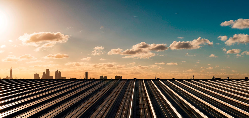 מבט מגג המבנה בכפר האולימפי אל הסקיי ליין של לונדון בשקיעה  (צילום: McCarragher Gilbert)