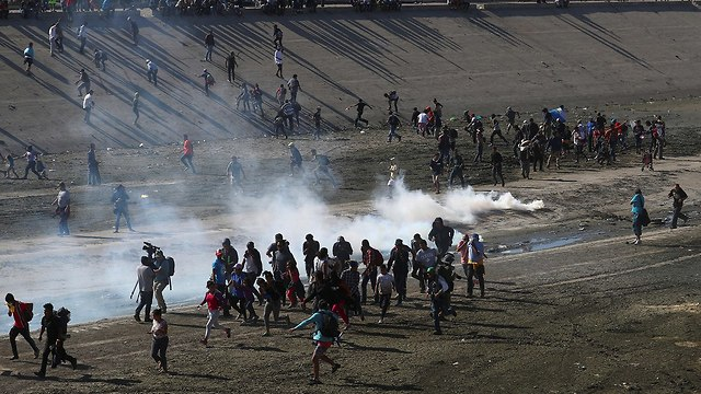 US border agents fire tear gas on hundreds of migrants protesting near the border with Mexico  (Photo: Reuters)