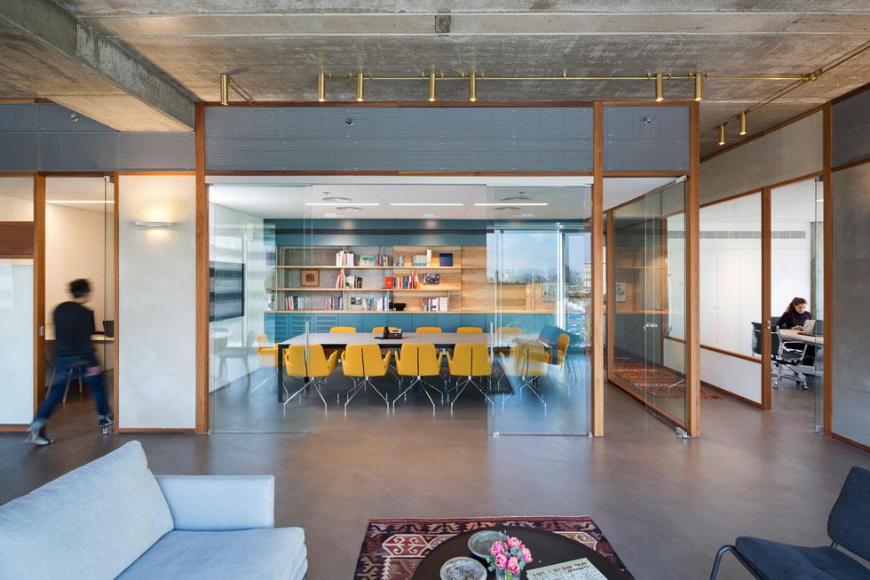 בין המרחב המשותף לחדר הישיבות ולחדרים הפרטיים חוצצים לוחות זכוכית שמוסגרו בעץ ארז, וההפרדה נראית אוורירית ונושמת (צילום: שי אפשטיין)