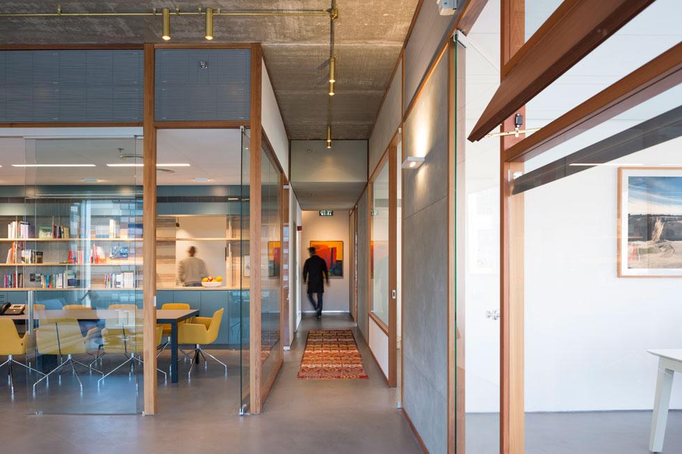 משרדי קרן לאוטמן ברמת החייל. מסדרון צר נפתח למרחב גדול, שעוצב באפור-בטון, זכוכית ועץ. שטיחים ועבודות אמנות מוסיפים חמימות (צילום: שי אפשטיין)