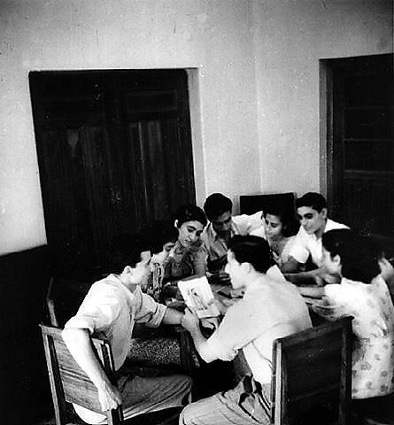 """קבוצה של חברי החלוץ לומדים עברית, עירק 1948 בקירוב - אחד התלמידים מחזיק בידיו תמונה של בנימין זאב הרצל (באדיבות אדיר שדה (המרכז לתיעוד חזותי ע""""ש אוסטר, בית התפוצות))"""