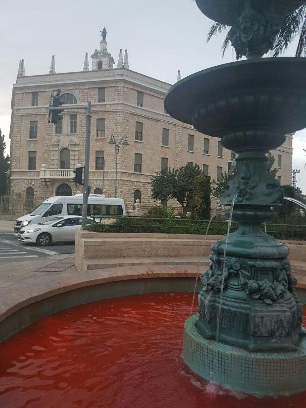 מזרקה בכיכר פריז בירושלים מלאה במים אדומים כמחאה באלימות נשים (צילום: פעילות לוט