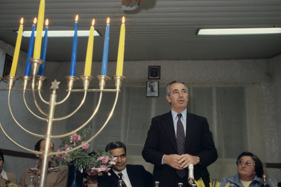"""ב-1980 היה שמעון פרס ח""""כ מטעם העבודה שנסע מסניף לסניף כדי לצבור תמיכה. בחנוכה הוא נסע לסניף ברמלה והדליק נרות עם מארחיו (צילום: דוד רובינגר)"""