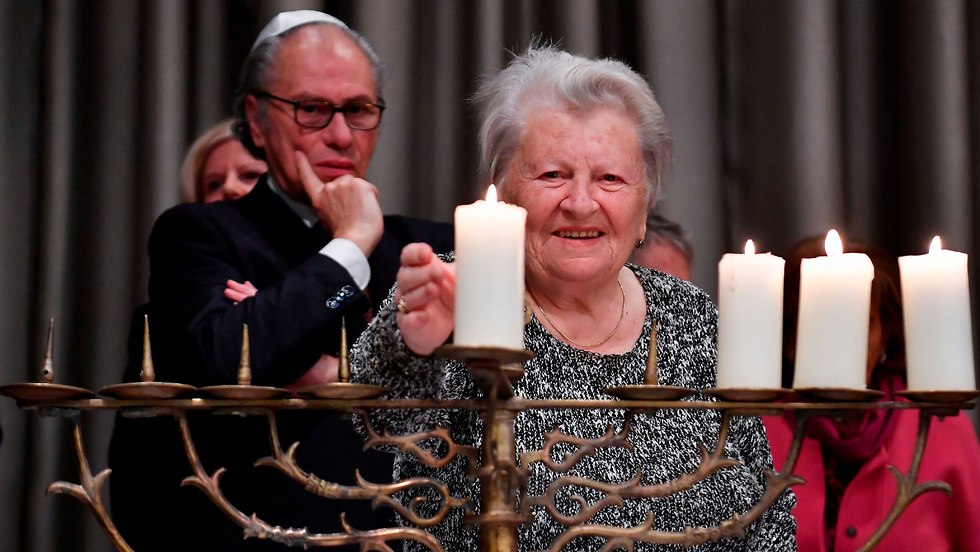 Holocaust survivor Assia Gorban lights a Hanukkah candle during the International Holocaust Survivors Night in Berlin (Photo: AFP)