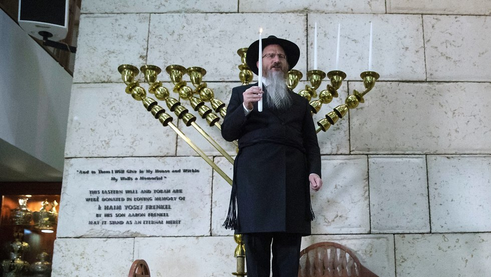 Russia's chief rabbi Berel Lazar, center, lights a Hanukkah candle during the International Holocaust Survivors Night of the Jewish Community at the Jewish Community Centre and Synagogue in Moscow (Photo: AP)
