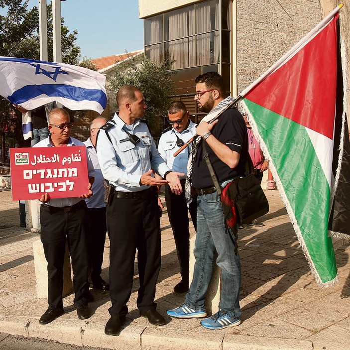 A police officer talks to Raja Za'atry as he carries a Palestinian flag during a demonstration
