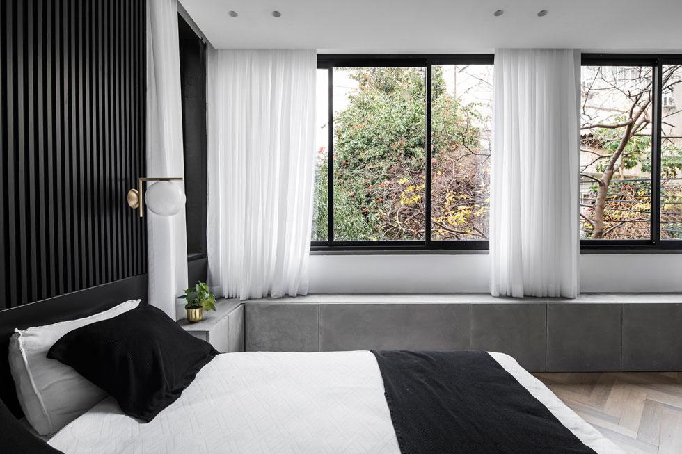בין אזור המיטה לחדר הרחצה יש קיר קטן ועליו טלוויזיה. הקיר יוצר פרטיות וגם מסתיר בתוכו עמוד קונסטרוקטיבי (צילום: איתי בנית)
