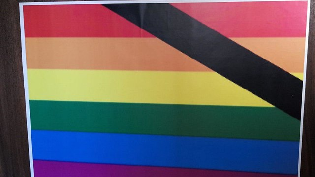 A poster that was put up outside home of men who have a Rainbow Flag on their balcony