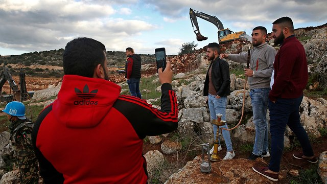 Lebanese villagers take souvenir pictures in front of Israeli excavators in the southern village of Mays al-Jaba (Photo: AP)