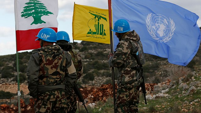 UN peacekeepers hold their flag while standing next to Hezbollah and Lebanese flags along the border (Photo: AP)