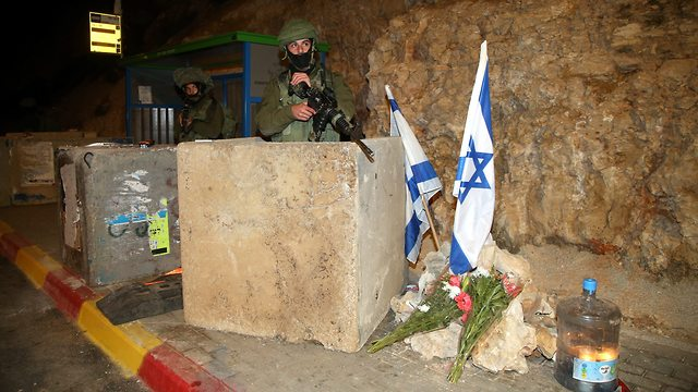 IDF soldiers securing hitchhiking stop in the West Bank