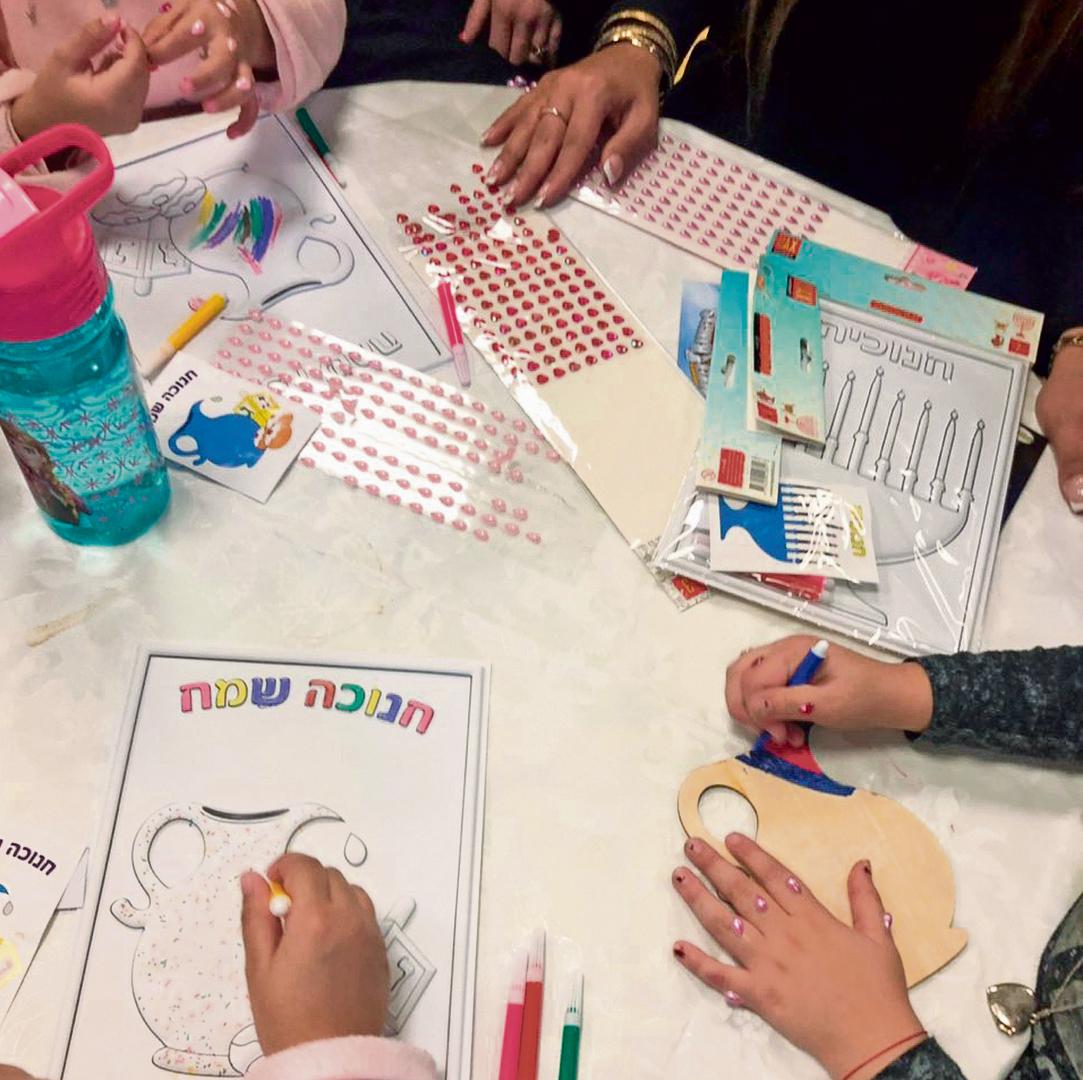Women and children make Hanukkah cards in the shelter