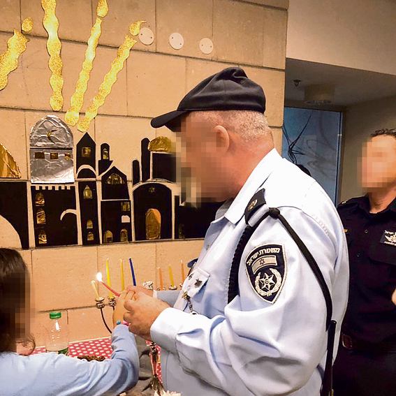 A police officer lights Hanukkah candles with the children in  the shelter