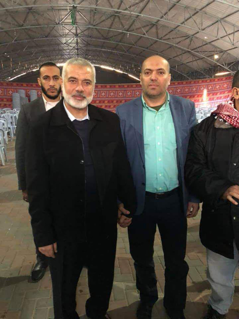 Jassar Barghouti holds hands with Hamas political leader Ismail Haniyeh in an image taken after the Ofra attack