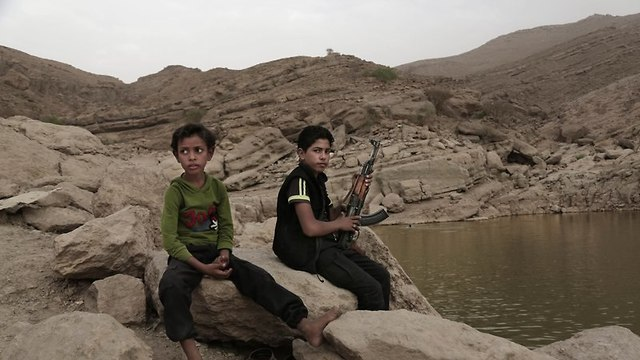 A 17 year-old boy holds his weapon in High dam in Marib.