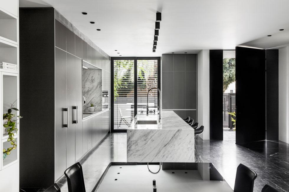 גם דלת הכניסה שחורה, והמטבח הפתוח, בחלקה הקדמי של הקומה, מתפרש מתחת לתקרה נמוכה. במרכזו תוכנן אי ארוך (ארבעה מטרים וחצי) לעבודה ואכילה, והוא כוסה במשטח בהיר של שיש קררה (צילום: איתי בנית)