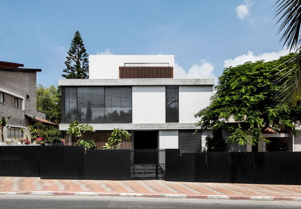 מצד הרחוב הבית נראה כבן שתי קומות רחבות, עם יחידה בנסיגה על הגג. גדר ברזל שחורה יוצרת לשני הבתים בדו-משפחתי חזית אחידה (צילום: איתי בנית)