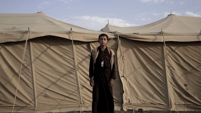 Sadek, a 14 year-old former child soldier, poses for a photograph at a camp for displaced persons where he took shelter with his family, in Marib.