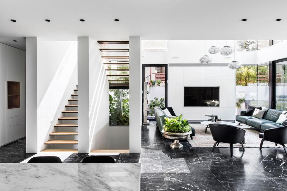 לסלון מרחב בגובה כפול. הספות שהובאו ממילאנו - כמו כל הרהיטים בבית - ניצבות זו מול זו על שטיח גדול. בין שתי הוויטרינות בחזית הצד תוכננה יחידת נגרות המסתירה את המערכות הטכניות ועליה מותקן מסך הטלוויזיה. גרם המדרגות מגדיר את גב הסלון (צילום: איתי בנית)