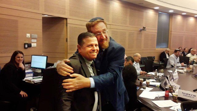 Across the aisle: Labor's Eitan Cable gets a hug from Yehuda Glick of Likud