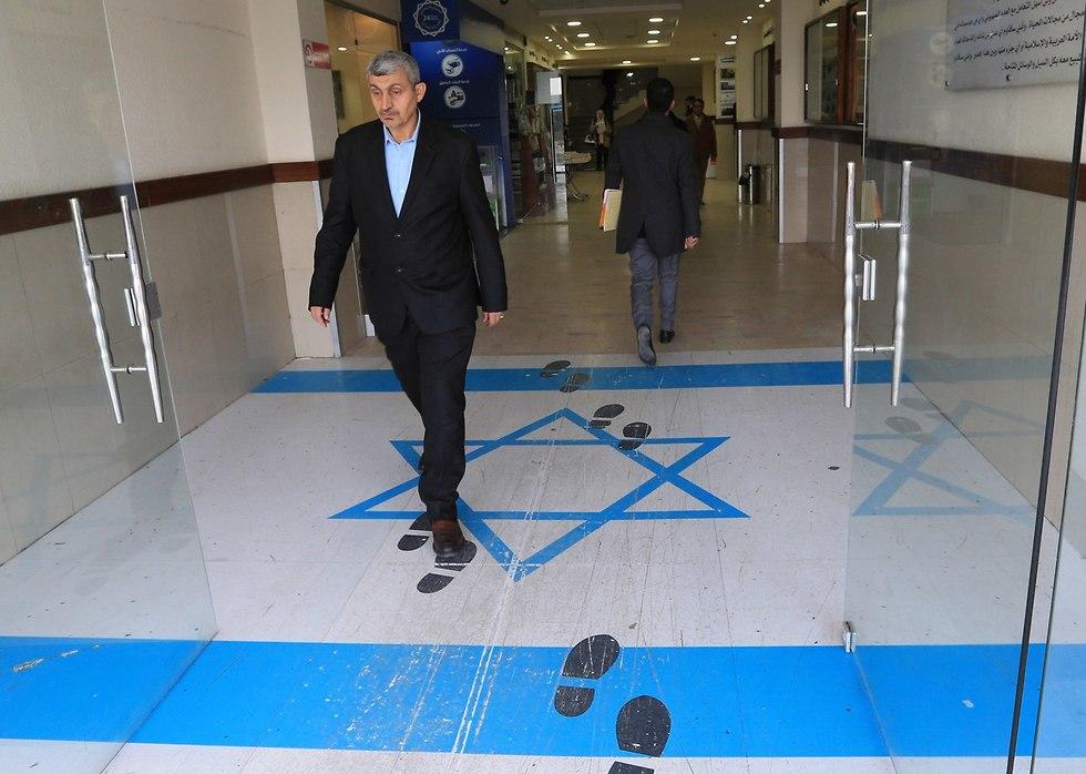 מבקרים במטה האיגודים המקצועיים בעמאן ירדן דורכים על דגל ישראל (צילום: AFP)