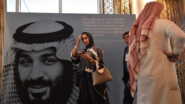 Participants at a Riyadh conference dedicated to enhancing Saudi youth learning and leadership walk in front of a portrait of Crown Prince Mohammed bin Salman last November. (Photo: Getty Images)