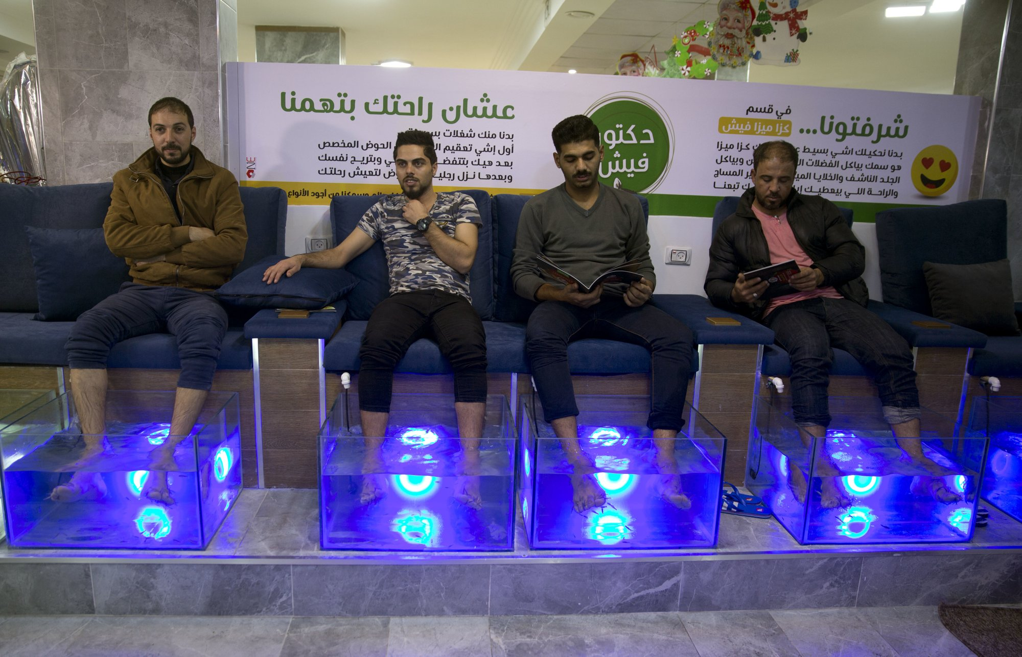 Palestinians soak their feet in tank stocked with fish at a cafe in Gaza City, December 26, 2018