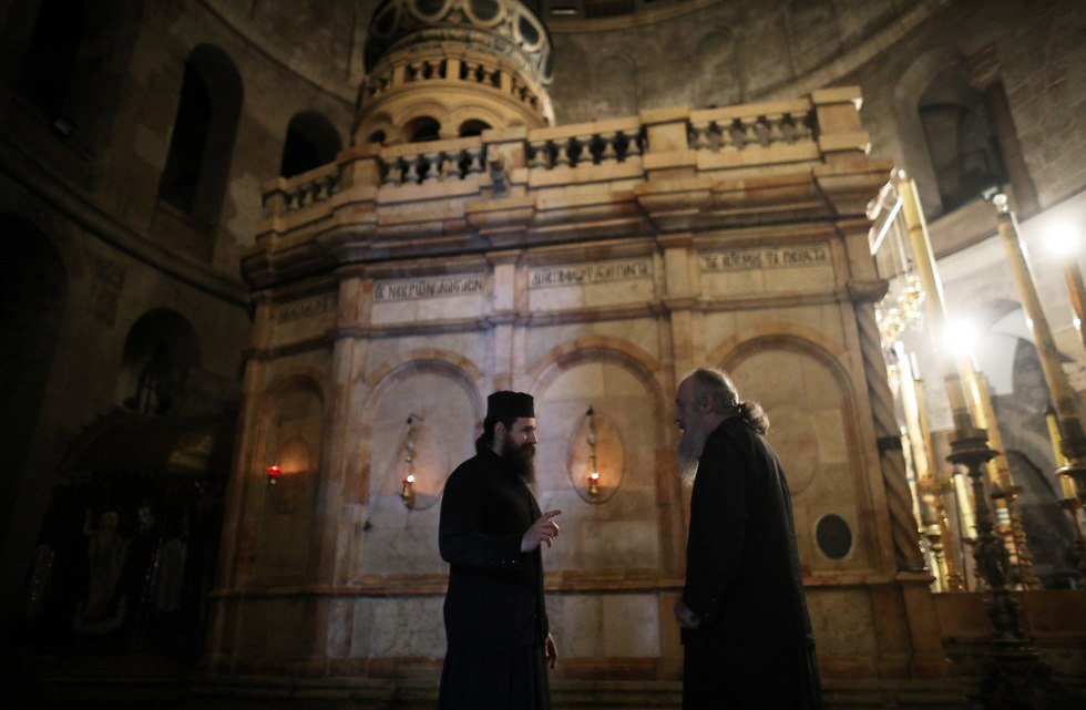 Orthodox Christian clergy converse in front of edicule
