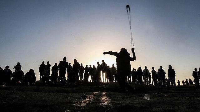 פלסטינים מפגינים מול גדר המערכת (צילום: AFP)