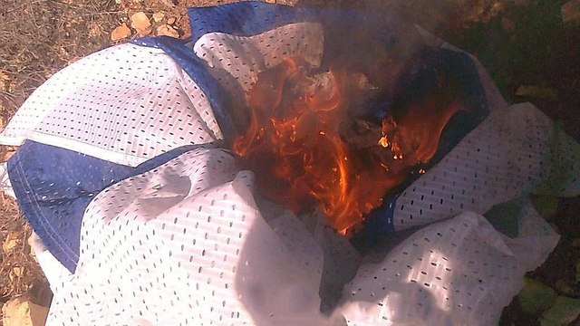 Israeli flag burned by Jewish minors (Photo: Shin Bet media)