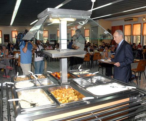 """שמעון פרס מבקר בניר-עם בתחילת שנות האלפיים, כשחדר האוכל עדיין היה פעיל (צילום: משה מילנר, לע""""מ)"""