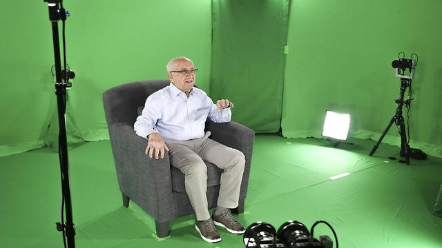 Holocaust survivor Max Glauben sitting in an interactive green screen room while filming a piece for