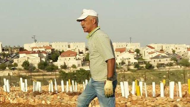 Rizq Salah working in the fields near Netiv Ha'avot