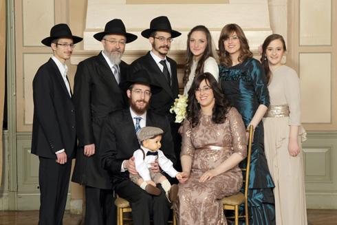 """אסתי גרינברג (בשמלה הירוקה) ומשפחתה. """"להביא את חום היהדות לאלסקה הקפואה"""" (צילום: Motti H -Mendel Meyers Studio)"""