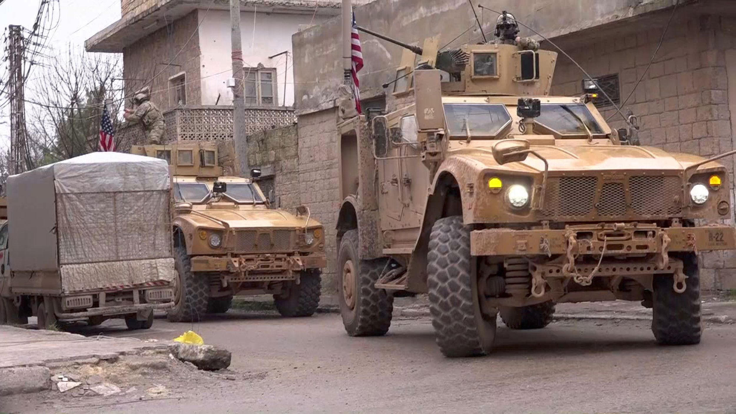 US armored vehicles at the scene of a suicide attack in the northern Syrian town of Manbij, January 16, 2019