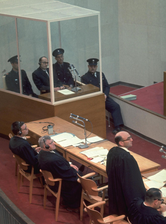 """האוזנר (מימין, עומד) באולם בית המשפט. בתא הזכוכית: אדולף אייכמן (צילום: מילי ג'ון, לע""""מ)"""