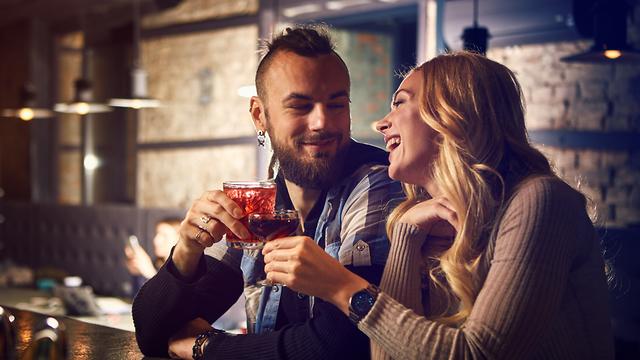 זוג מפלרטט על הבר (צילום: Shutterstock)