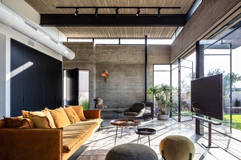 """עם תקרה בגובה ארבעה מטרים, התחושה היא של מרחב. הקירות עשויים בטון חשוף עם דוגמת נקייה של הקרשים והחורים של תבניות היציקה. הרצפה, בהתאמה, עשויה בטון מלוטש עם אגרגטים גדולים. """"הפשטות והישירות הזו היא סוג האסתטיקה שחיפשנו כאן""""  (צילום: עמית גרון)"""