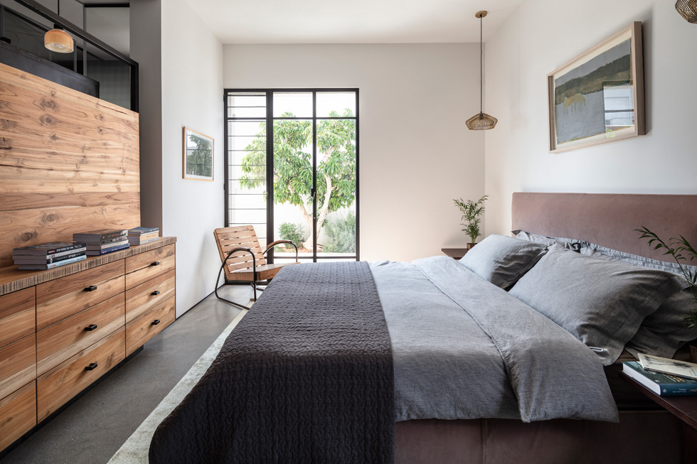 גם חדר ההורים תוכנן כמרחב פתוח. המיטה עומדת מול רהיט דו-צדדי שעשוי מעץ מלא ומסגרת ברזל, והוא משמש כאן כשידת מגירות נמוכה (צילום: עמית גרון)