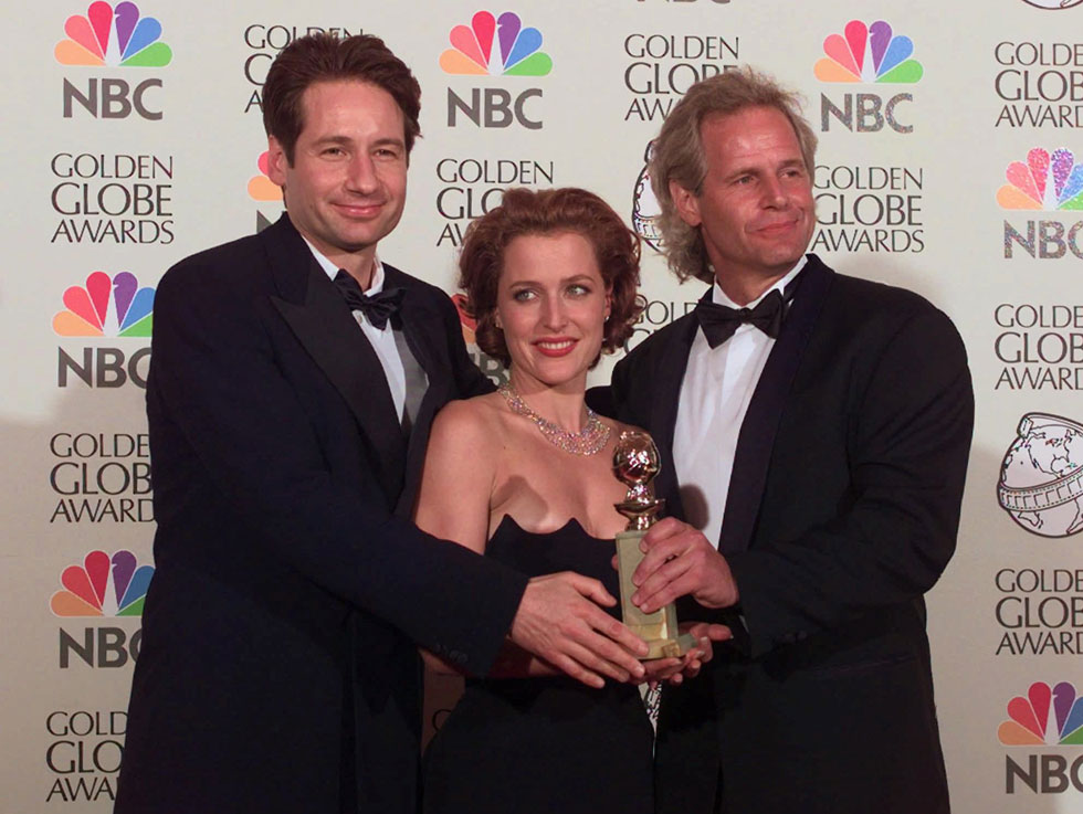 """אנדרסון עם יוצר הסדרה """"תיקים באפלה"""" (מימין) והפרטנר דייוויד דוכובני בטקס גלובוס הזהב 1998 (צילום: AP)"""