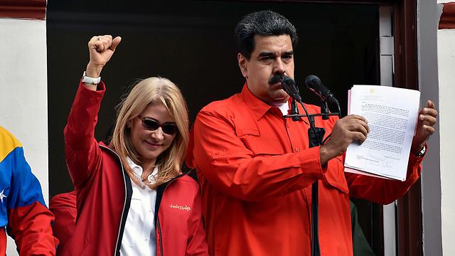 נשיא ונצואלה ניקולאס מדורו  עם אשתו וסגן הנשיא מול קהל ב קראקס (צילום: AFP)