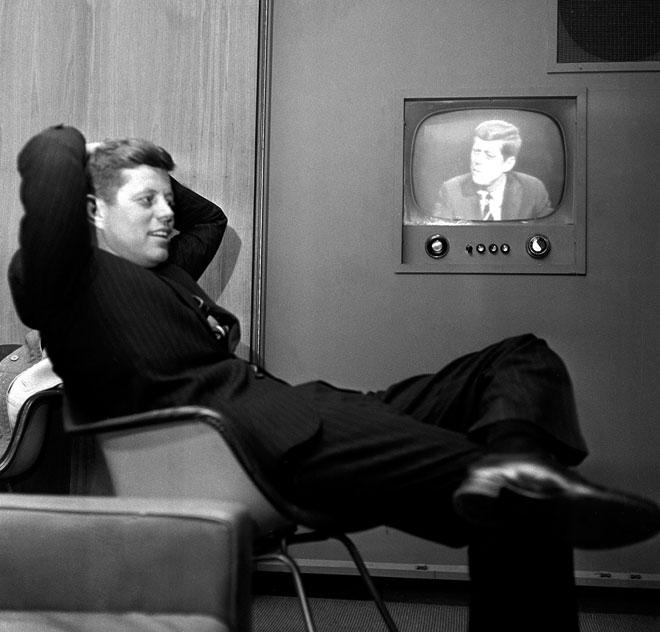 """המועמד לנשיאות קנדי צופה בעצמו מדבר בטלוויזיה, 1960.""""החזקים הוגנים, החלשים מובטחים והשלום נשמר""""  (צילום: AP)"""