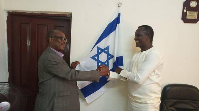 Adikalie Foday Sumah, left, at the Sierra Leone parliament with the Israeli flag