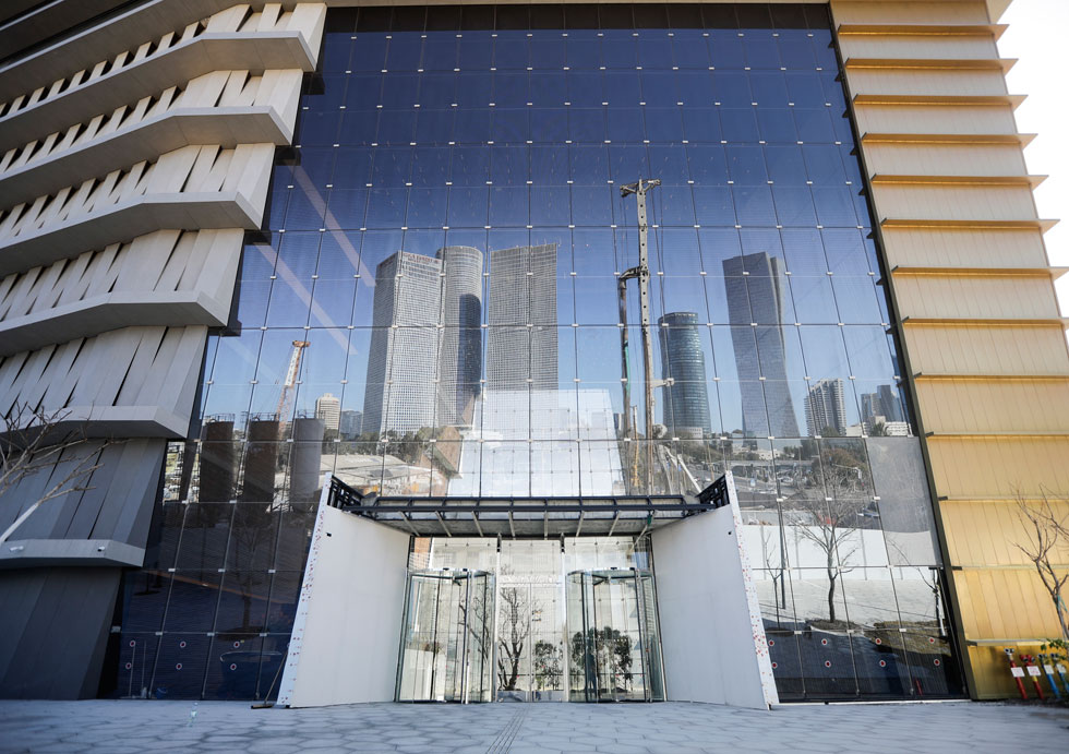 מגדלי עזריאלי משתקפים בקיר הכניסה ללובי. רון ארד וישר אדריכלים תכננו מבנה גרנדיוזי וראוותני, שנראה אחרת מכל צד שלו (צילום: איל מרילוס)