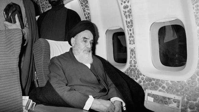 Ayatollah Ruhollah Khomeini sits inside the chartered airplane in Paris before flying back to Iran after 14 years of exile.