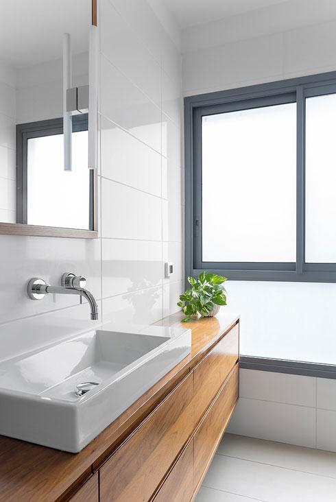 חדר הרחצה של ההורים. אריחים לבנים פשוטים, ברז וכיור משודרגים, וארון כיור בגוון הפרקט (צילום: שי אפשטיין)