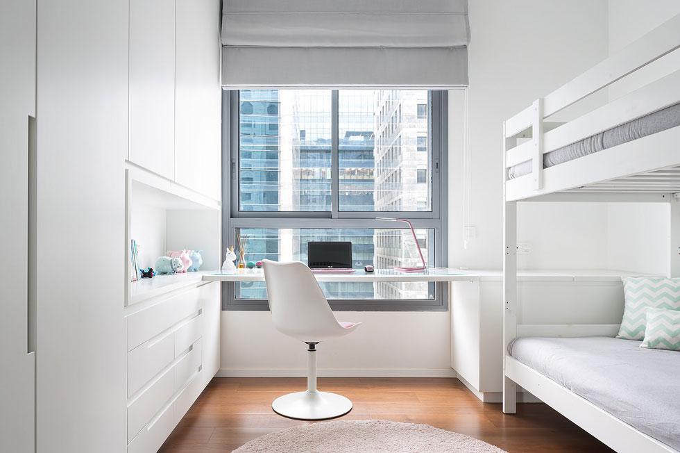 שתי הילדות חולקות חדר. שולחן הכתיבה משקיף על מגדלי המשרדים ברחוב הארבעה. הוא עוצב כפתרון לחלונות המגדל, שלא תמיד מתאימים לשימושים של חדר שינה  (צילום: שי אפשטיין)